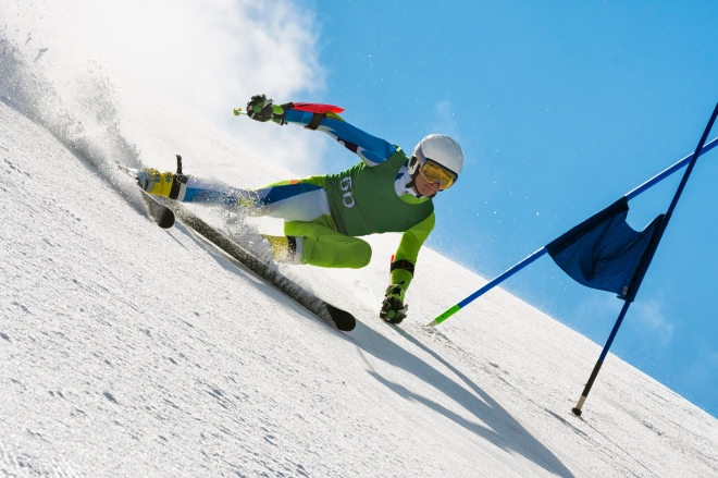 Professional Alpine Skier Compeeting at Giant Slalom Race Against the Blue Sky