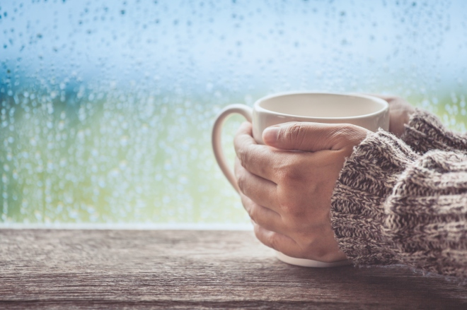 Woman hand holding the cup of coffee or tea on rainy day window background